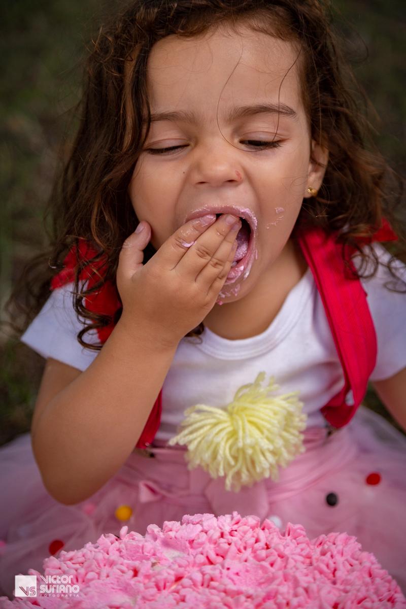 menina fecha os olhos ao colocar pedaço de bolo na boca se deliciando com o doce em ensaio smash the cake.