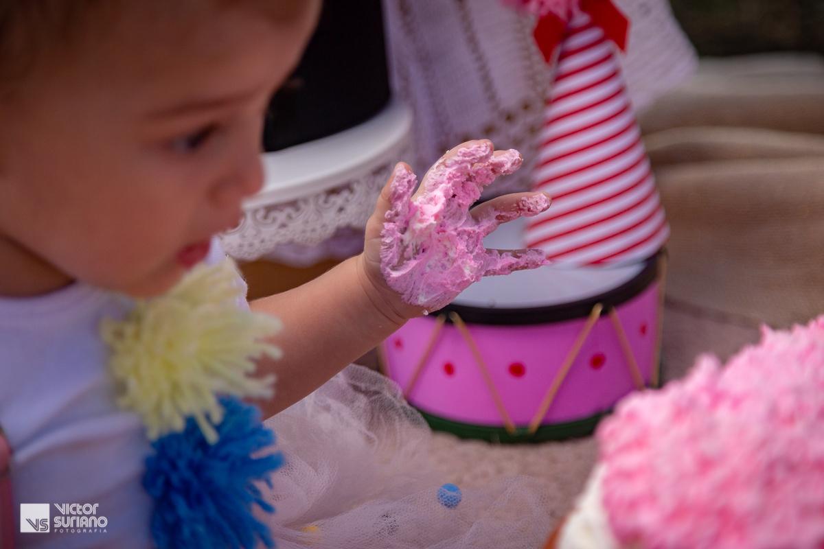 destaque para mão de menina suja com bolo cor de rosa em ensaio fotográfico smash the cake com tema circo rosa.