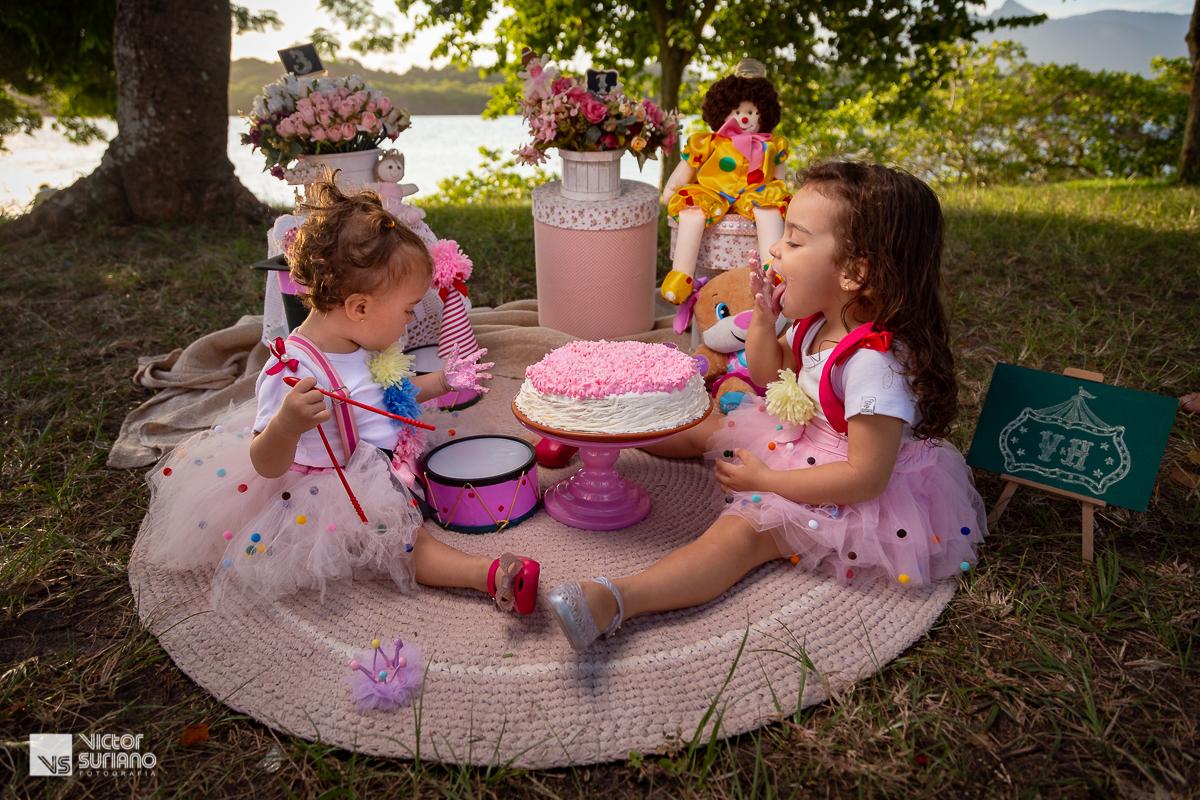 irmãs atacando o bolo rosa, sujando as mãos com o bolo em ensaio smash the cake na beira do rio e barra de são João.