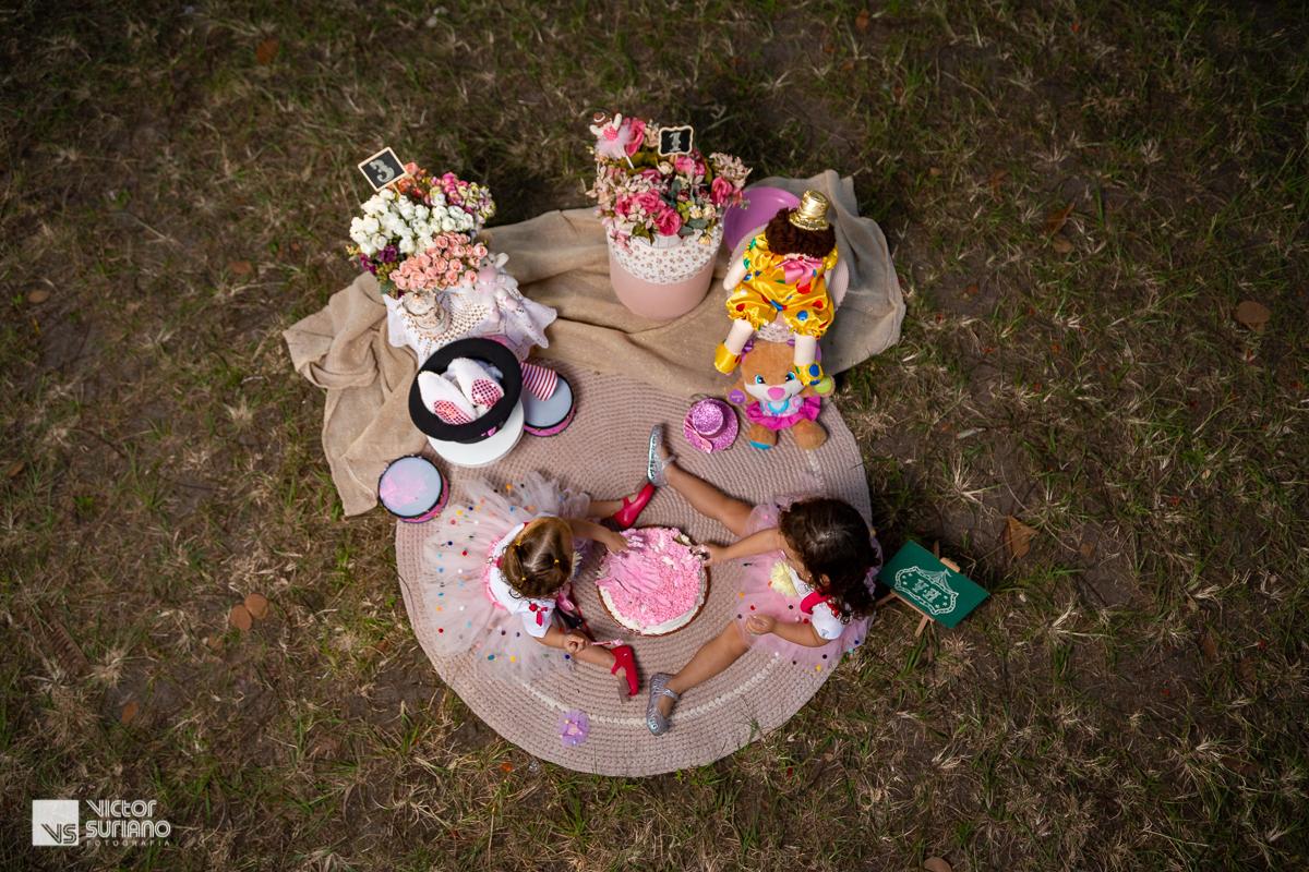visão do alta da ornamentação de cenário para ensaio fotográfico smash the cake com crianças sentadas com bolo rosa no meio das pernas abertas.