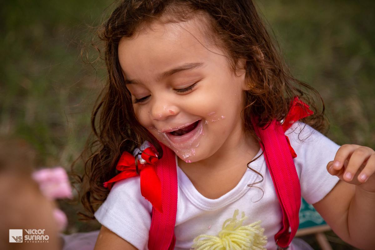 menina sorrindo e olhando para o bolo rosa que está destruindo no ensaio smash the cake com tema circo rosa