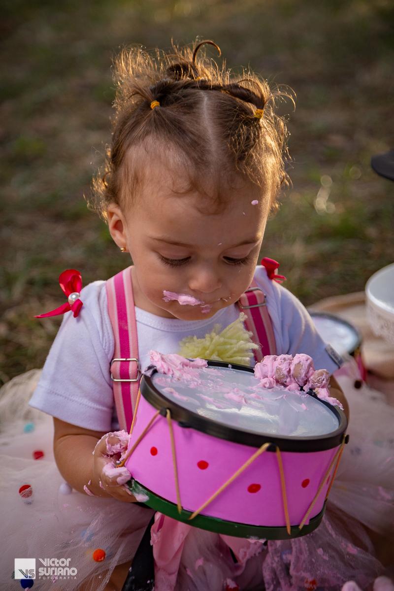 menina com a boca e as mão sujas de bolo rosa em ensaio fotográfico smash the cake tema circo rosa