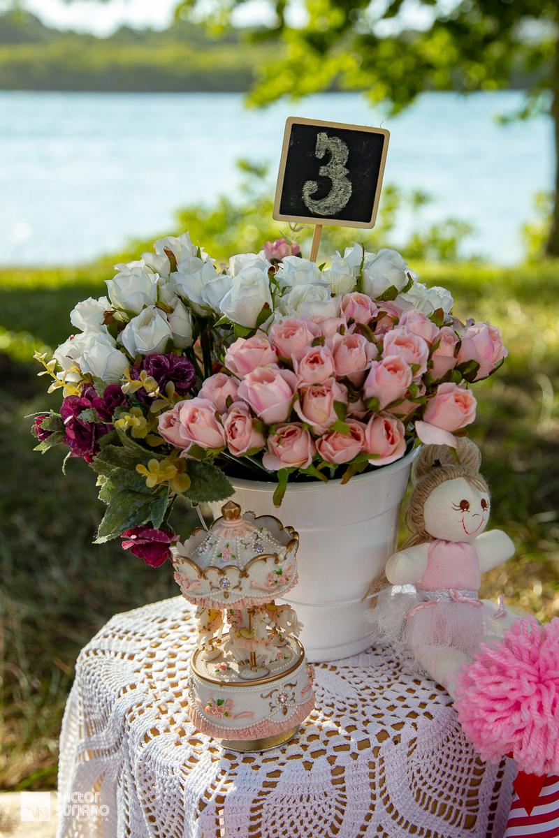 vaso de flores artificiais e boneca de pano usados na decoração de cenário para ensaio fotográfico smash the cake com tema circo rosa.