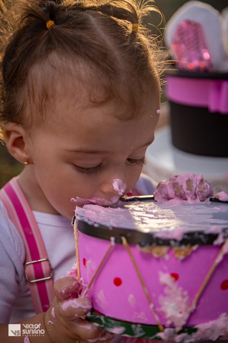 menina lambendo tamborzinho de brinquedo sujo de bolo rosa em ensaio fotográfico smash the cake tema circo rosa.