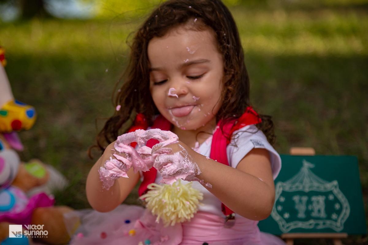 menina com a língua de fora e com as mãos sujas de bolo rosa faz coração para a mamãe