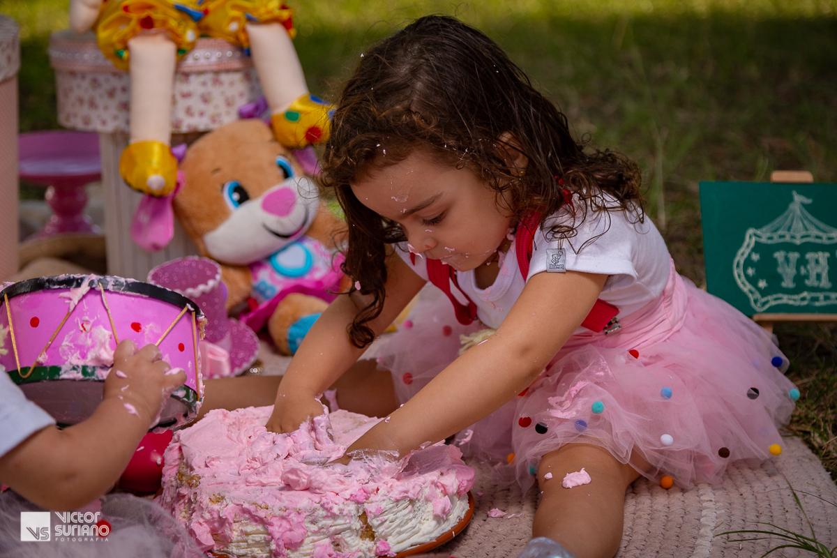 menina bate com força no bolo rosa do ensaio smash the cake sujando as mãos e pernas