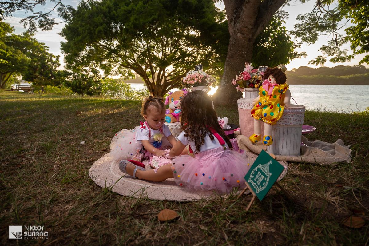 irmãs brincando de se suja com bolo rosa em ensaio smash the cake na beira do rio em barra de são João