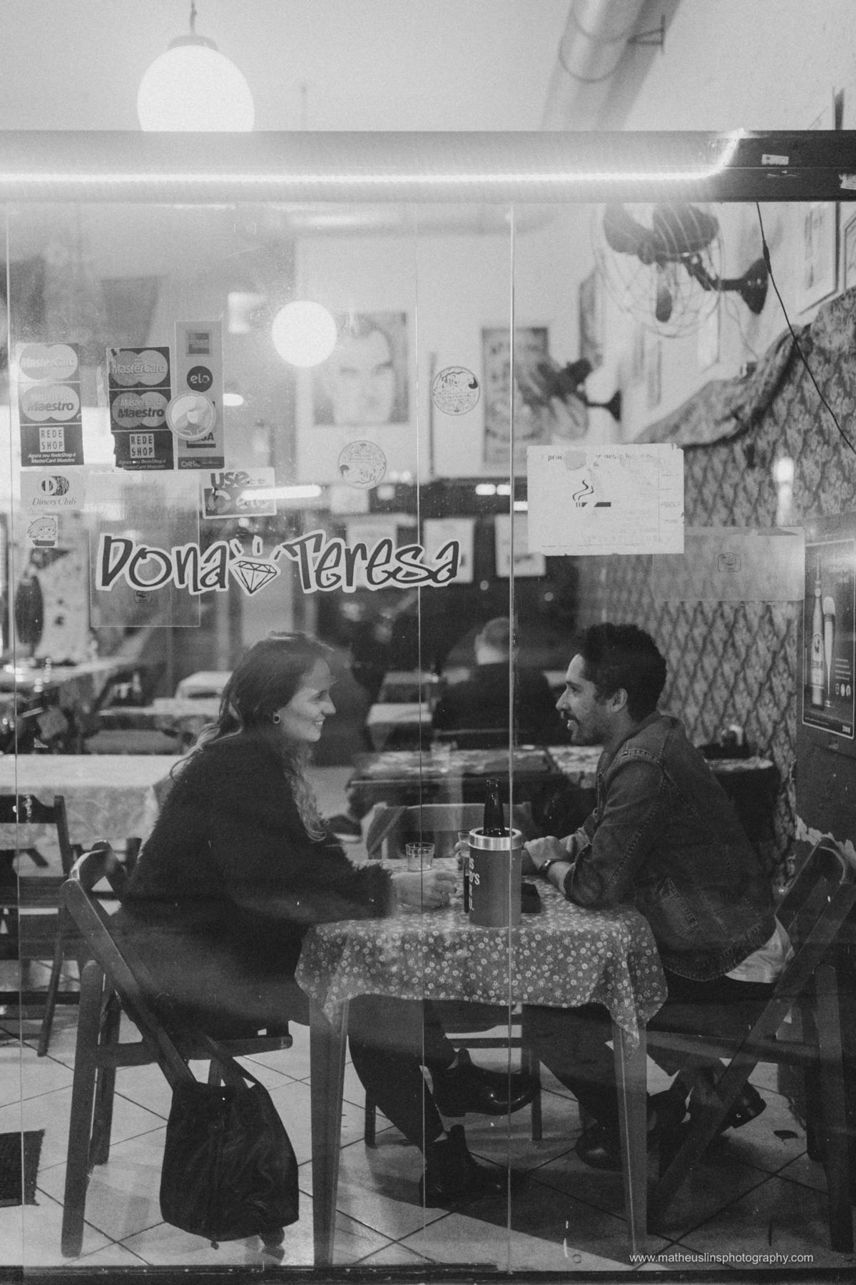 ensaio de casal realizado em são paulo na rua augusta durante a noite. o casal esta sorrindo em um bar