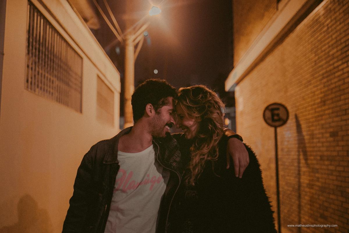 ensaio de casal realizado em são paulo na rua augusta durante a noite. o casal esta sorrindo sentados na rua namorando.