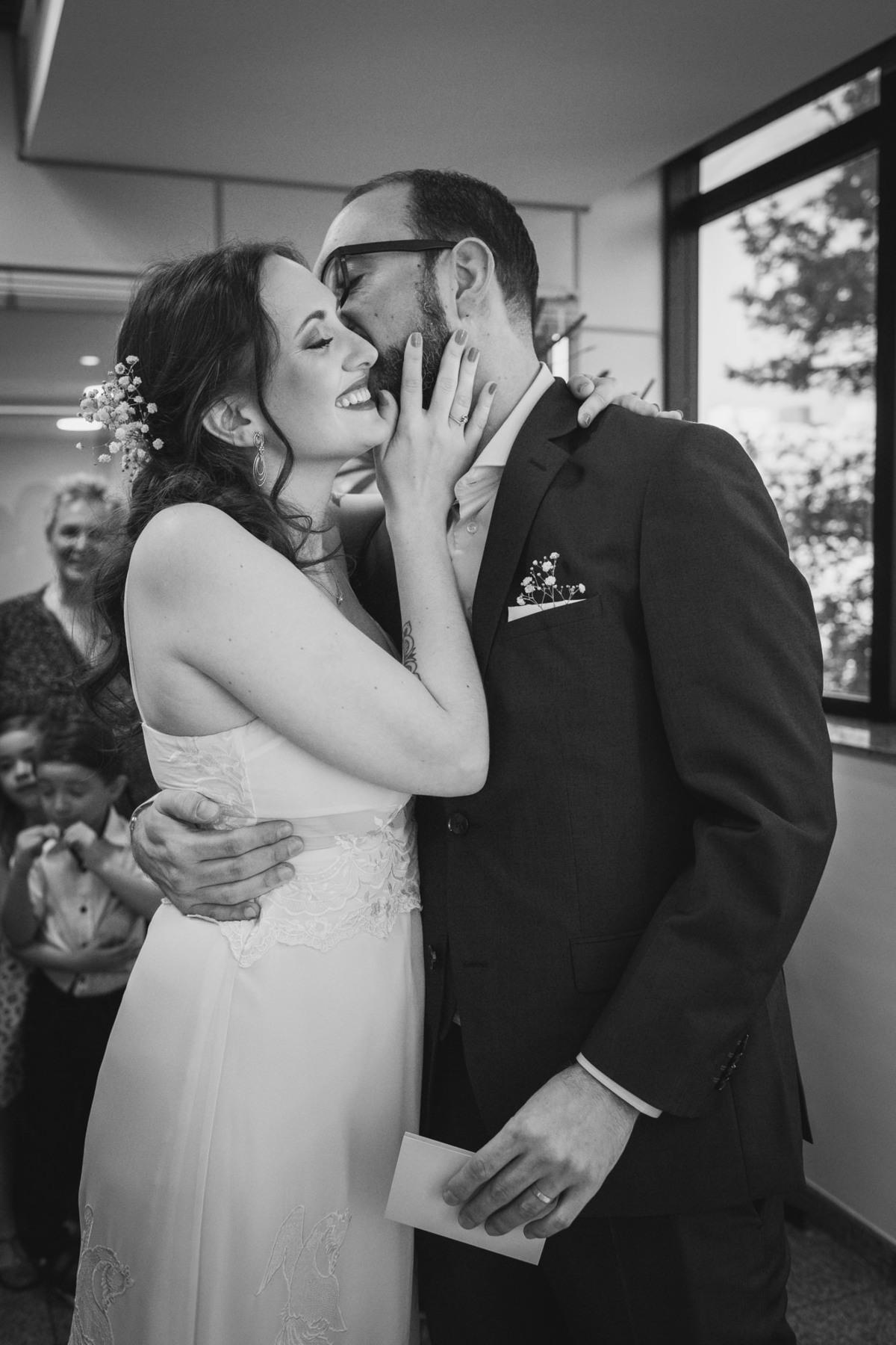 noivo beijando noiva no rosto em casamento civil