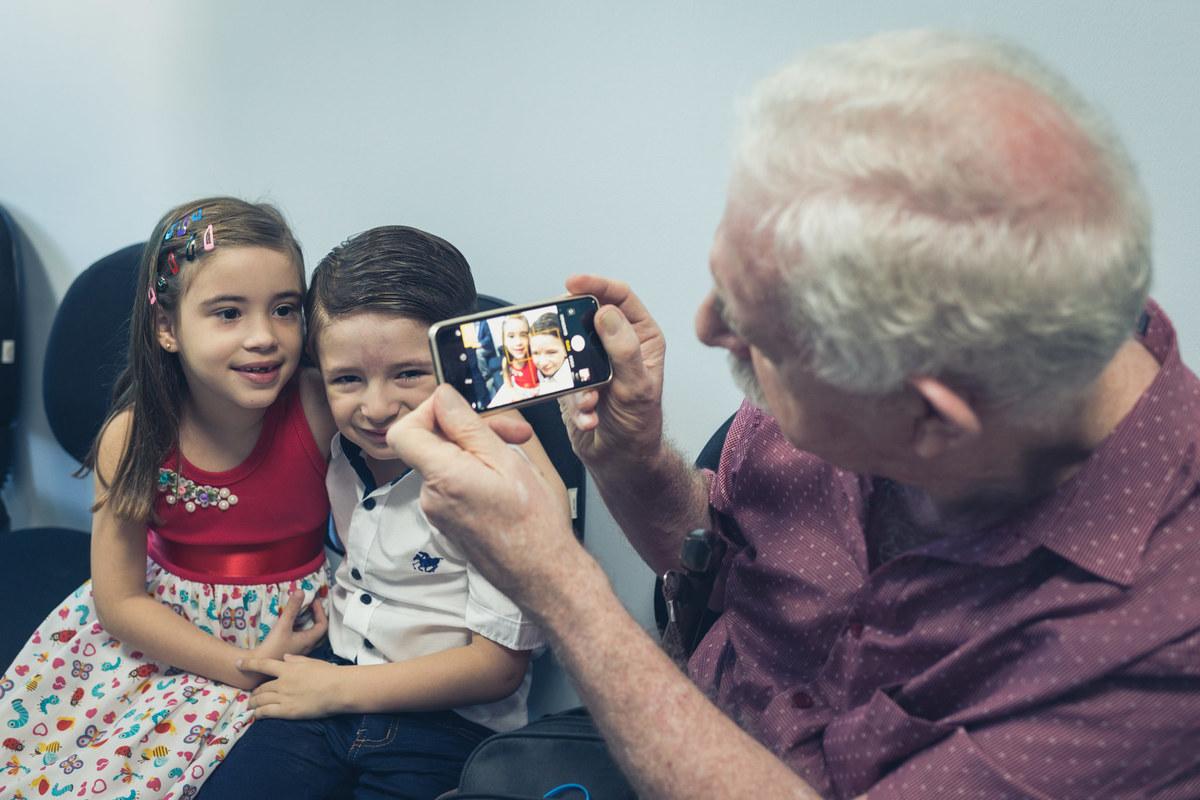 avô tirando foto dos netos
