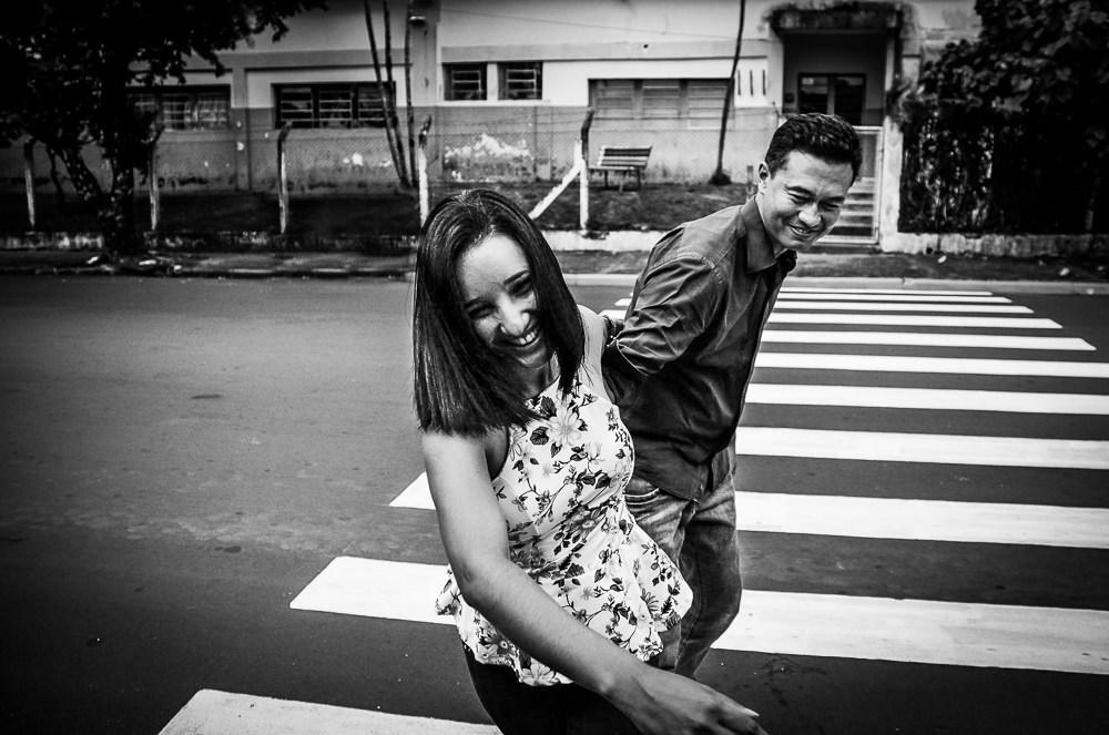 Casal de noivos sorrindo andando na rua na faixa de pedestres em Araçatuba, SP