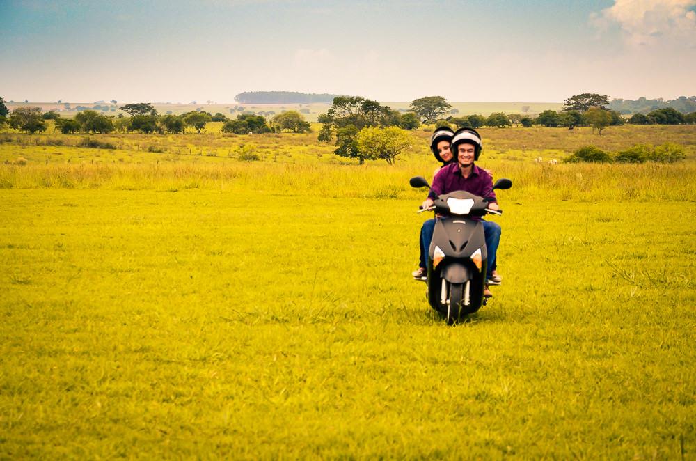 Casal de noivos guiando a moto no campo com gramado verde e usando capacete no ensaio fotográfico pre casamento em Araçatuba, SP