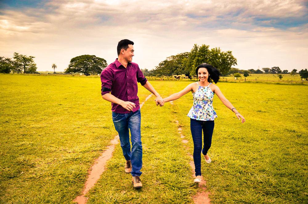 O noivo e a noiva correndo no campo com gramado verde, felizes de mãos dadas em Araçatuba, SP