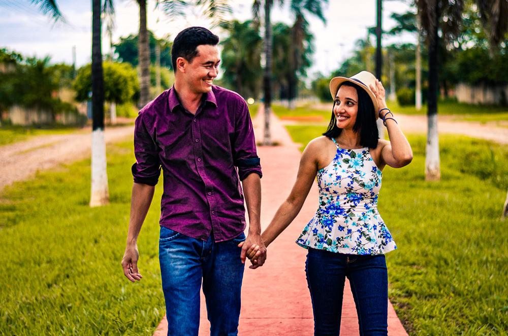 Ensaio fotográfico pre casamento. Os noivos estão caminhando de mãos dadas se olhando e sorrindo em Araçatuba SP