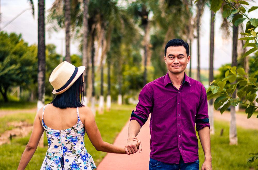 Fotografia do noivo e da noiva no ensaio pre casamento ou wedding, ela está de costas usando chapéu e ele de frente, estão de mãos dadas. Em Araçatuba, SP