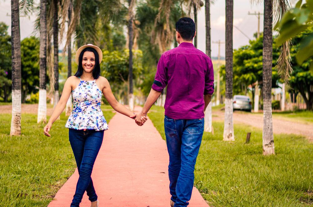 Fotografia do casal de noivos no ensaio pre casamento ou wedding. Estão caminhando, ela de frente e ele de costas e de mãos dadas em Araçatuba, SP