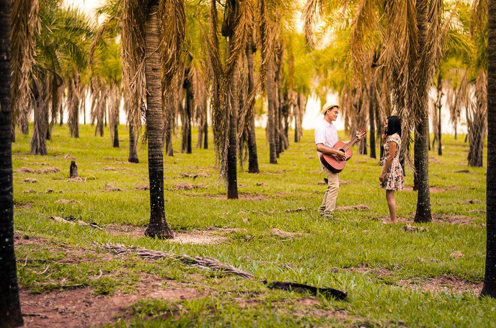 Fotografia do ensaio de pre casamento ou wedding dos noivos em um campo aberto com muitas plameiras e sol. Estão próximos, ele toca uma canção no violão para ela. Em Araçatuba, SP