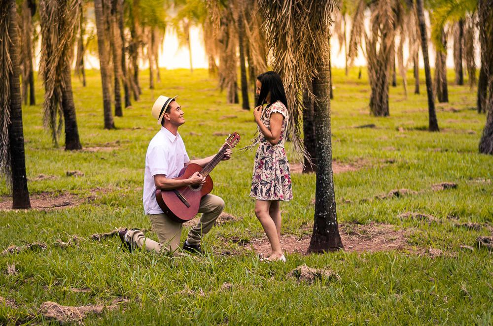 Fotografia do ensaio de pre casamento ou wedding dos noivos em um campo aberto com muitas plameiras e sol. Estão próximos, ele toca uma canção no violão para ela de joelhos. Em Araçatuba, SP
