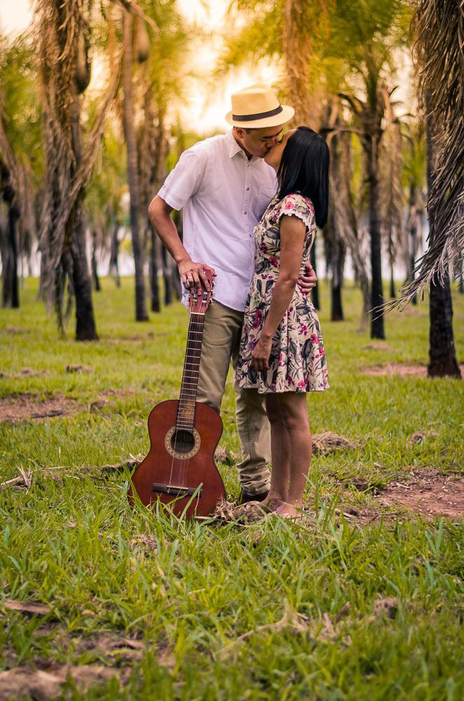 Fotografia do ensaio de pre casamento ou wedding dos noivos em um campo aberto com muitas plameiras e sol. Estão se beijando e eles segura seu violão. Em Araçatuba, SP