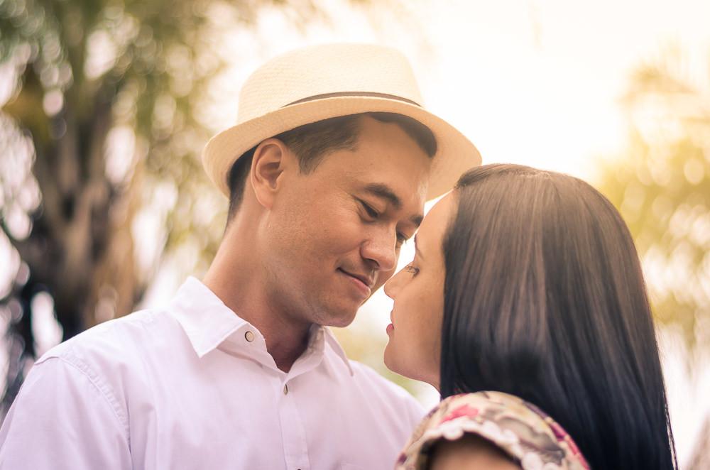 Fotografia do ensaio de pre casamento ou wedding do casal de noivos em Araçatuba, SP. Estão com os rostos bem próximos e se olhando com ternura. Um dia ensolarado, ele usa chapéu.