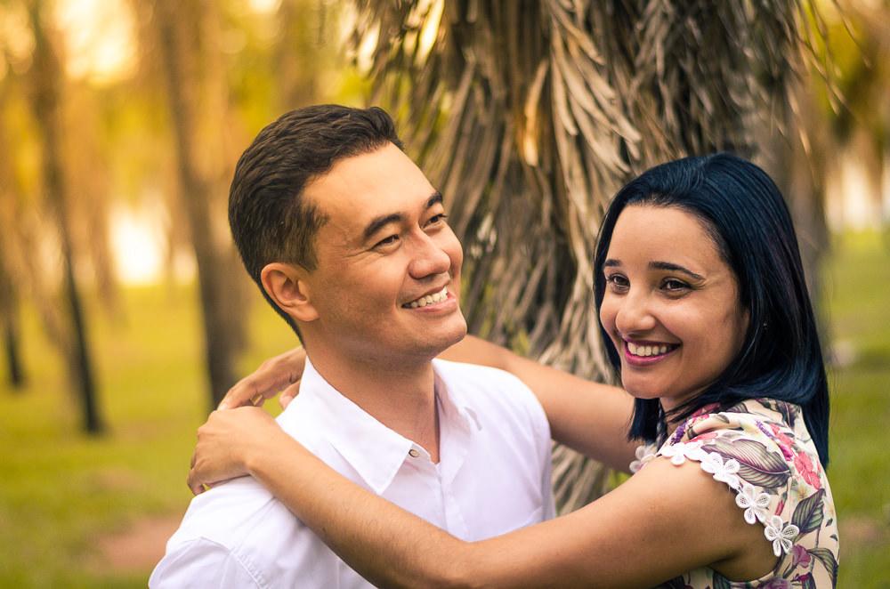 Fotografia no campo ensolarado na natureza com palmeiras ao fundo do casal de noivos no ensaio pre casamento ou wedding. Ela abraça o noivo e ambos sorriem com satisfação.