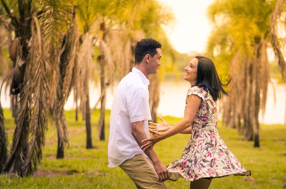 Fotografia no campo com sol e palmeiras ao fundo e o rio Tietê do noivo e da noiva no ensaio pre casamento ou wedding em Araçatuba, SP