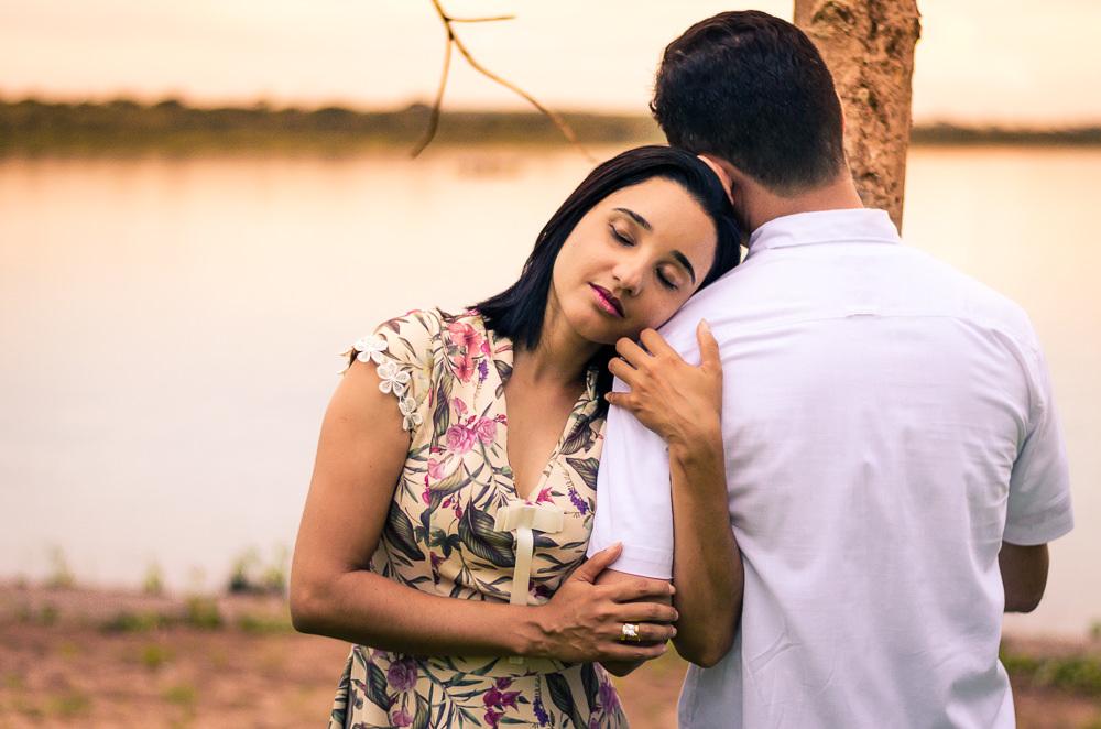 Fotografia com o rio Tietê no por do sol do noivo e da noiva no ensaio pre casamento ou wedding se abraçando com ternura em Araçatuba, SP
