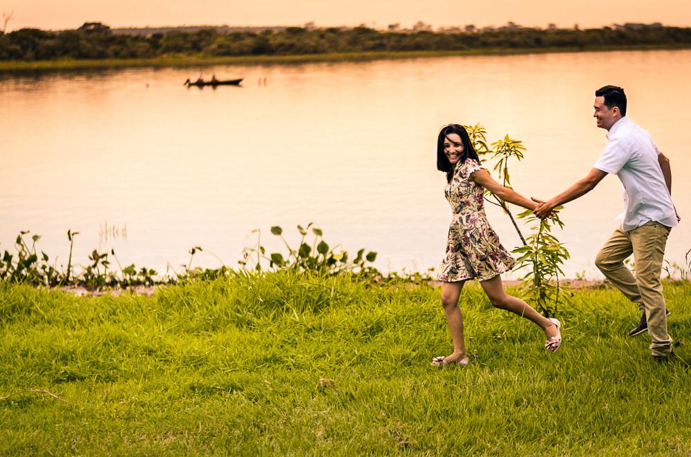 Fotografia com o rio Tietê no por do sol do noivo e da noiva no ensaio pre casamento ou wedding correndo de mãos dadas e sorrindo em Araçatuba, SP