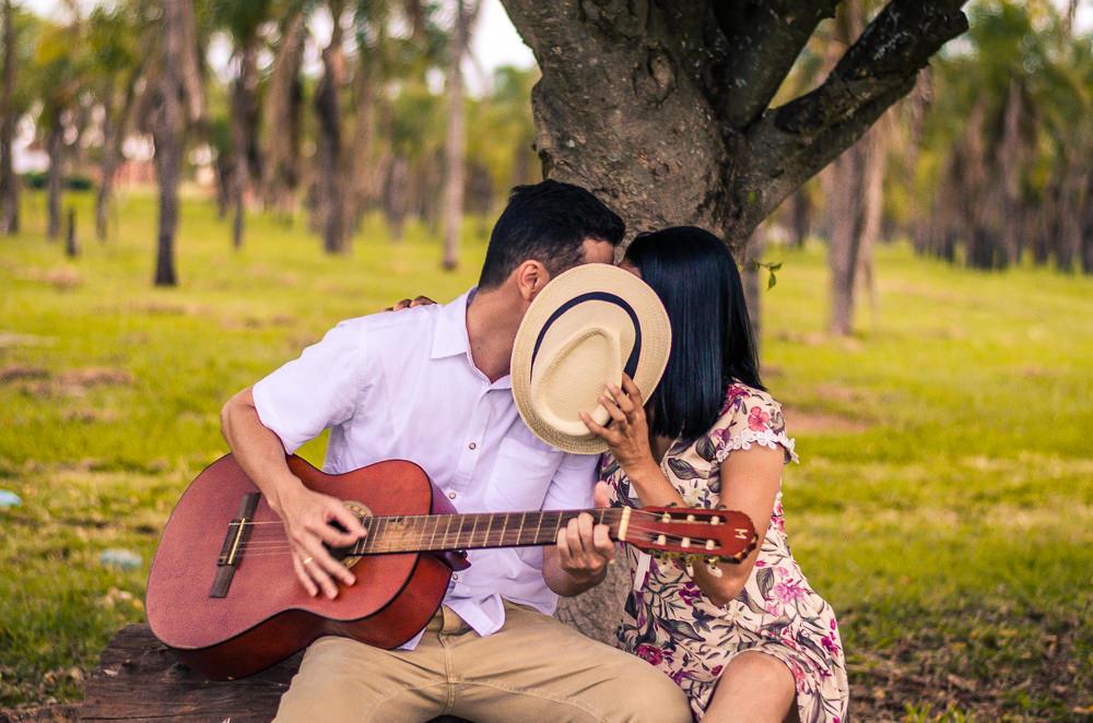 Ensaio pre casamento ou wedding do casal de noivos em Araçatuba, SP. Estão sentados, ele toca uma música no violão e ela tampa o rosto dels com um chapéu.