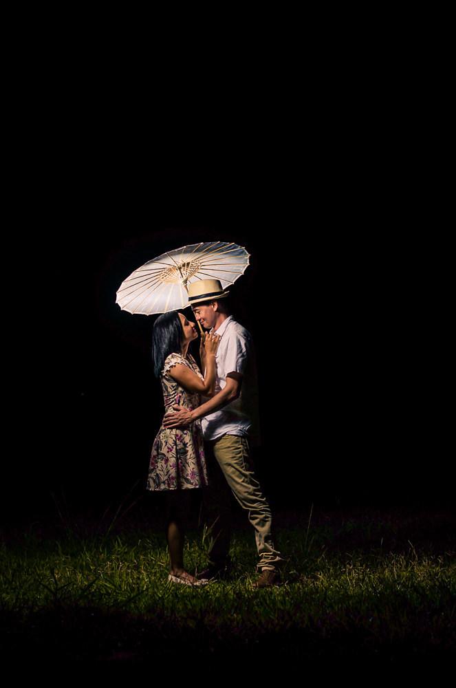 Fotografia do ensaio pre casamento ou wedding do casal de noivos em Araçatuba, SP. Está a noite estão se abraçando e se olhando com carinho, ele usa chapéu e com uma sombrinha japonesa, Wagasa