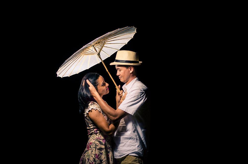 Fotografia do ensaio pre casamento ou wedding do casal de noivos em Araçatuba, SP. Está a noite estão se abraçando e se olhando com carinho, ele usa chapéu e com uma sombrinha japonesa, Wagasa.