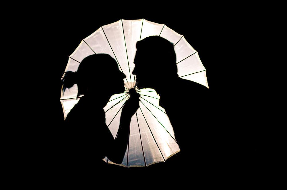 Fotografia do ensaio pre casamento ou wedding do casal de noivos em Araçatuba, SP. Está a noite e estão bem próximos, quase se beijando atrás de uma sombrinha japonesa, Wagasa