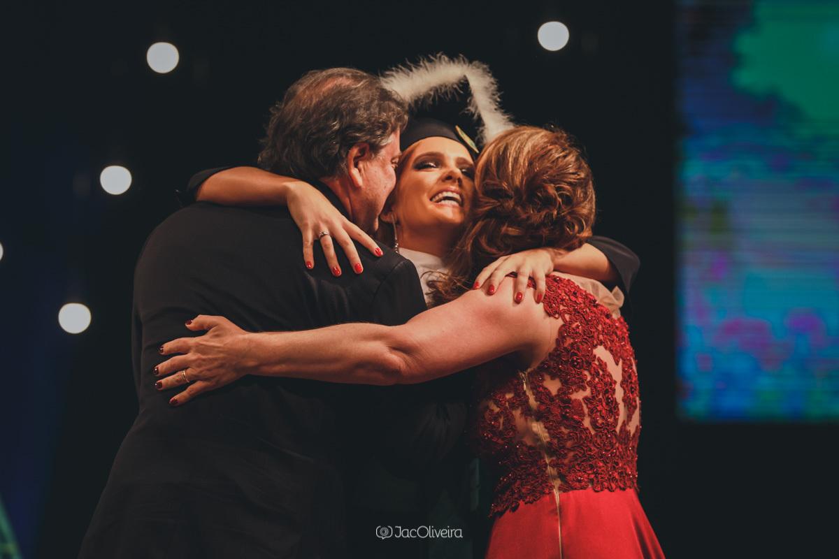 fotografa formatura colação de grau porto alegre; formanda abraça pais no palco