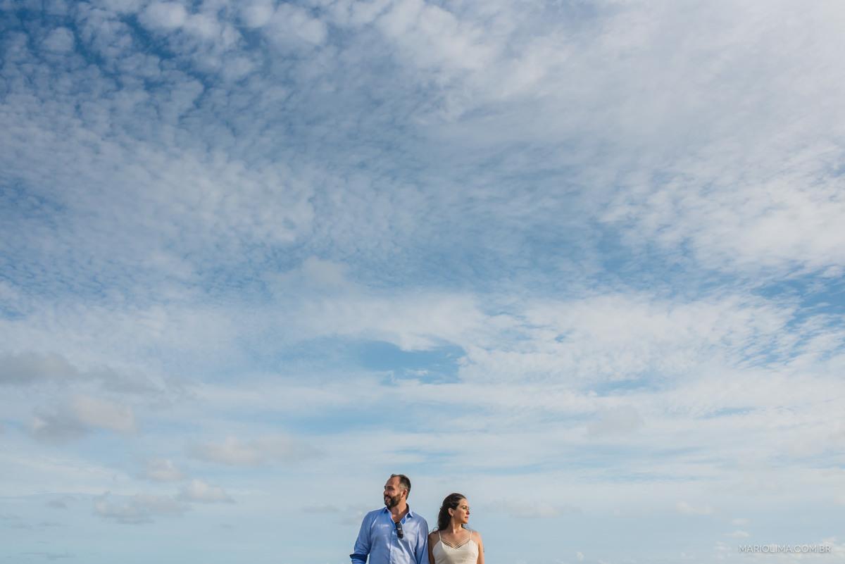 retrato dos noivos com céu azul e nuvens no ensaio pré-casamento na praia de Riviera