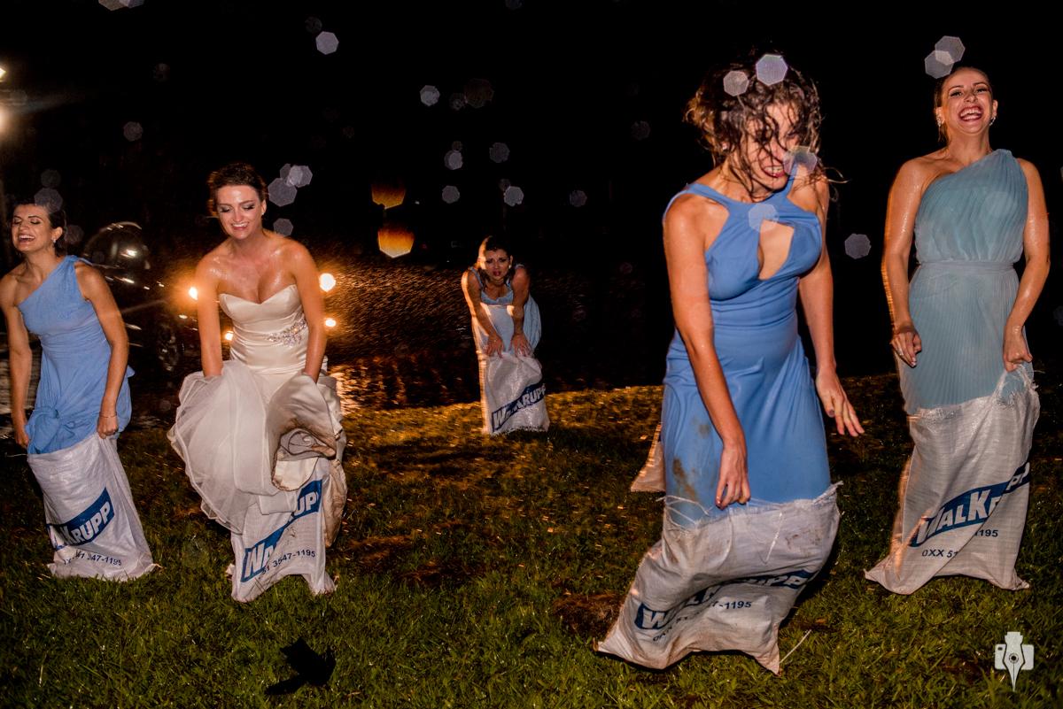 noiva e madrinhas pulando com o saco no casamento