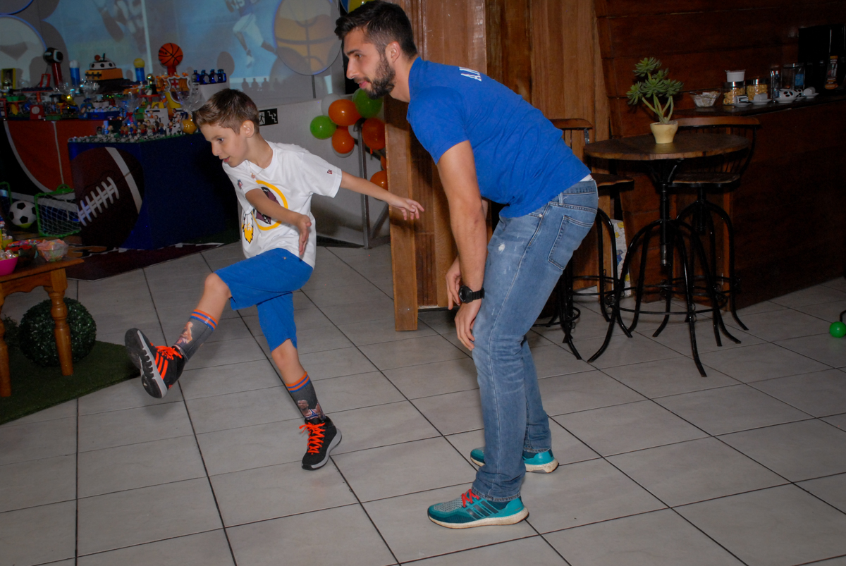 O aniversariante brinca com seu padrinho no Buffet Fábrica da Alegria, Osasco, Sao Paulo, tema da festa esportes americanos, aniversariante Matheus 8 anos