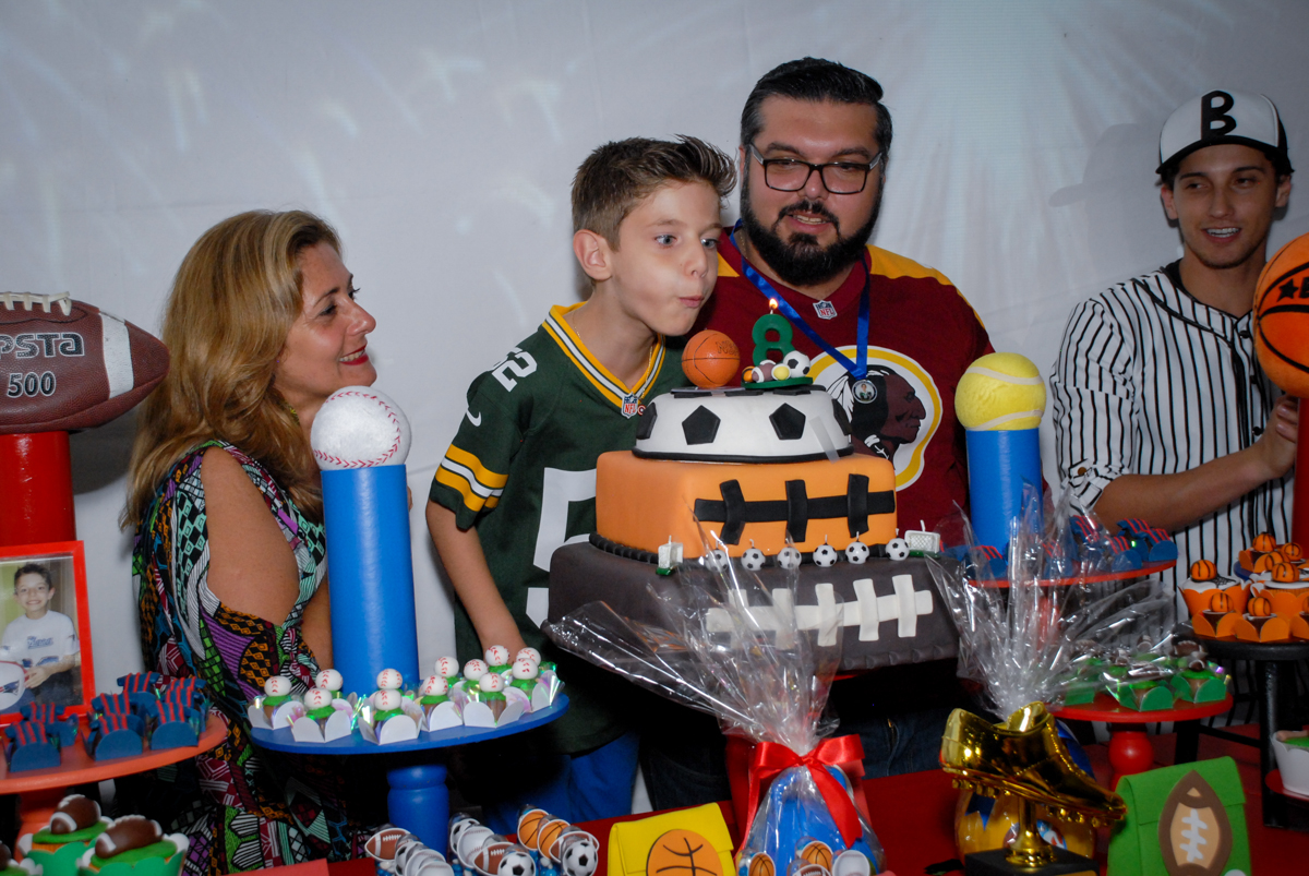 assoprando a vela do bolo no Buffet Fábrica da Alegria, Osasco, Sao Paulo, tema da festa esportes americanos, aniversariante Matheus 8 anos