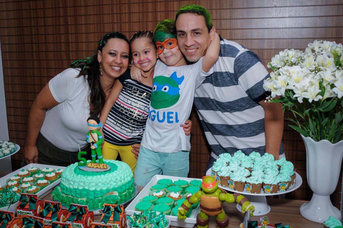 a família é fotografada na mesa do bolo no Condomínio Vila Leopoldina, festa infantil, tema Tartaruga Ninja, Miguel 5 anos