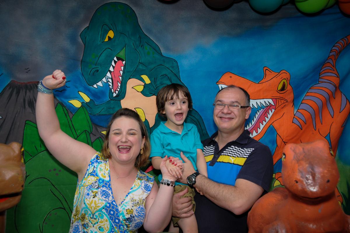 fotografia da família em frente a mesa decorada no Buffet Planeta 2, Butantã, SP, festa infantil fotografia infantil, aniversário de Fabrício 4 anos tema da mesa dinossauros