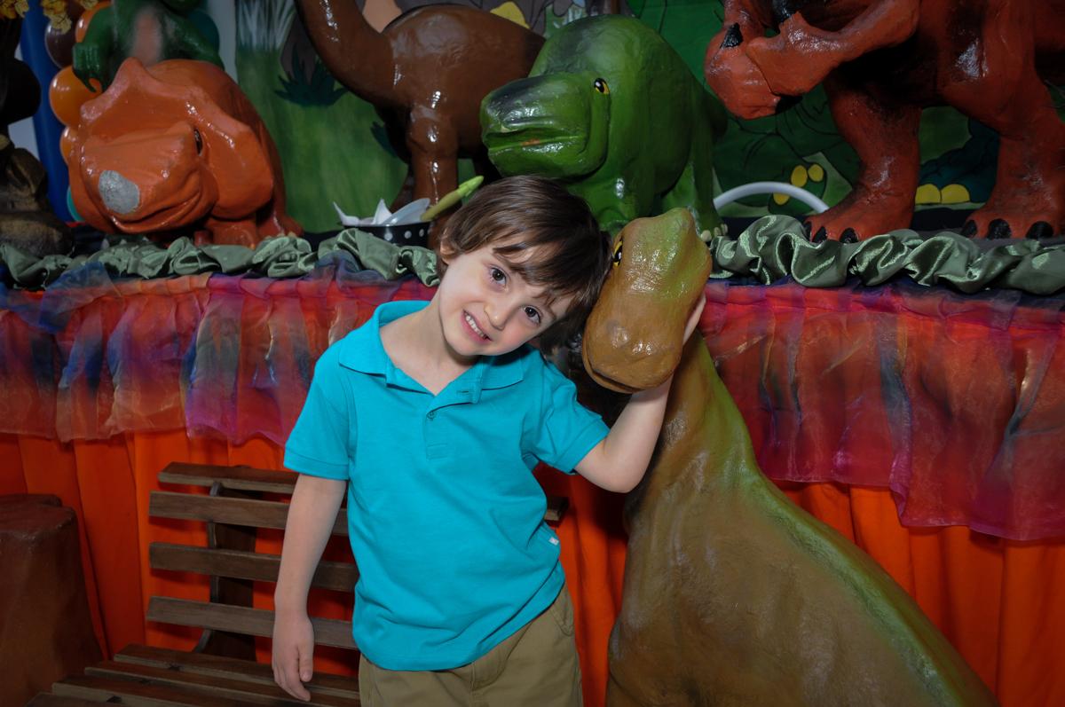 fotografia do aniversariante em frente a mesa decorada no Buffet Planeta 2, Butantã, SP, festa infantil fotografia infantil, aniversário de Fabrício 4 anos tema da mesa dinossauros