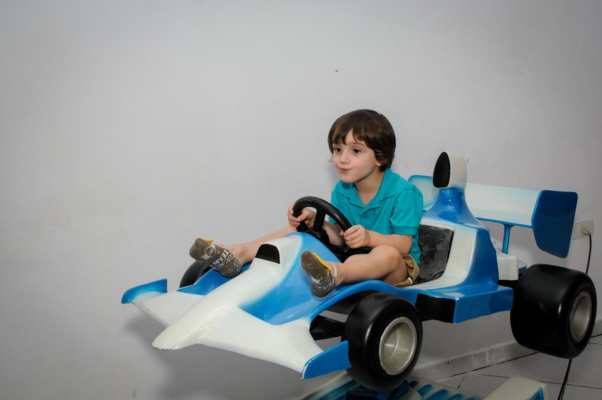 brincando no carrinho de corrida no Buffet Planeta 2, Butantã, SP, festa infantil fotografia infantil, aniversário de Fabrício 4 anos tema da mesa dinossauros