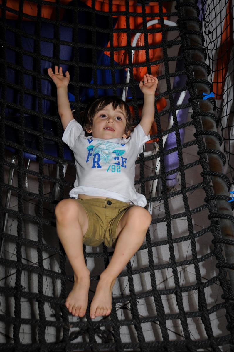 deitado relaxando no brinquedão no Buffet Planeta 2, Butantã, SP, festa infantil fotografia infantil, aniversário de Fabrício 4 anos tema da mesa dinossauros
