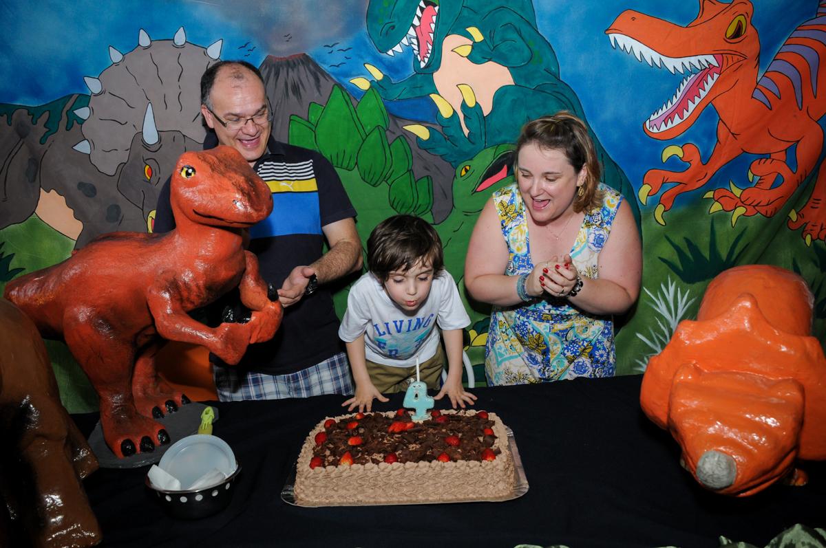soprando a velinha do bolo no Buffet Planeta 2, Butantã, SP, festa infantil fotografia infantil, aniversário de Fabrício 4 anos tema da mesa dinossauros