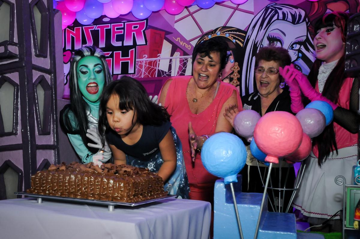 soprando a vela do bolo na Festa Raquel 5 anos no Buffet Balakatoon, Jabaquara, SP, tema da festa Monster High