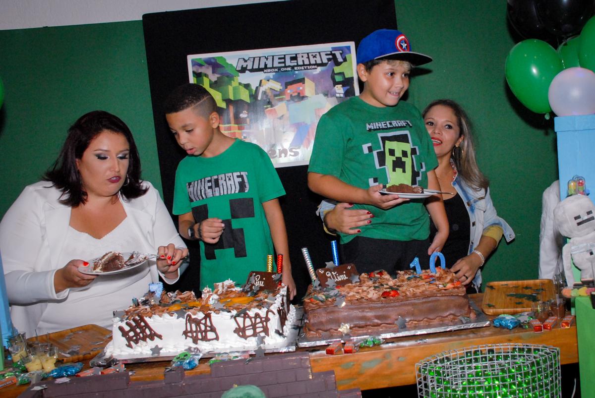 cortando o primeiro pedaço de bolo na Festa infantil, festa de Vinícius 10 anos tema da mesa minicraft, no Buffet Fábrica da Alegria, Morumbi,SP