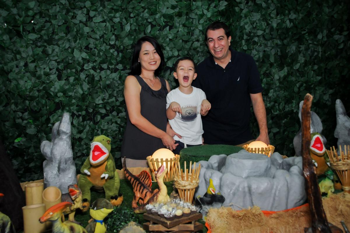 Foto da família na mesa decorada no FestaInfantil, fotografia infantil aniversário de Rafael 3 anos tema da festa Dinossauros no Buffet Mago Ra Tim Boom, Saúde, SP