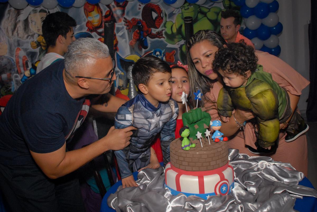 soprando a vela do bolo no Buffet Galeria da Arte, Vila Maria, São Paulo, aniversário de Lorenzo 4 e Lucca 1 aninho tema da festa super herois