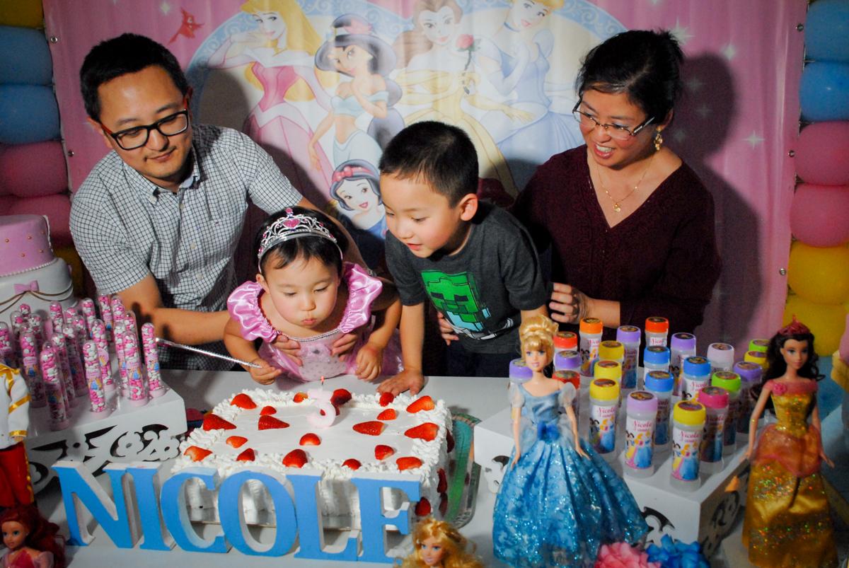 soprando a vela do bolo no condominio vila mariana aniversario de nicole 3 aninhos tema da festa princesas
