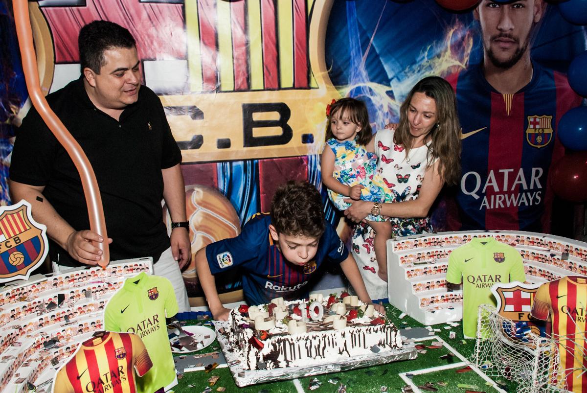 soprando a vela do bolo no Buffet Planeta Kids, aniversário de Gustavo 10 anos, tema da festa Barcelona